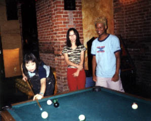 Michie from Shonen Knife hustles Mike Randle of Baby Lemonade at pool